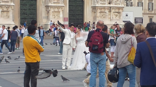 Casal tirando fotos com os pombos na Piazza del Duomo